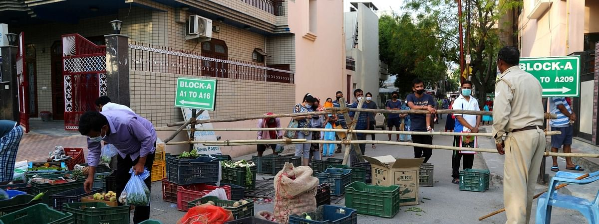 People waiting in a queue to buy vegetables and fruits in their residential colony which has been sealed as one of the hotspots for COVID-19 cases, in Noida on April 11, 2020.