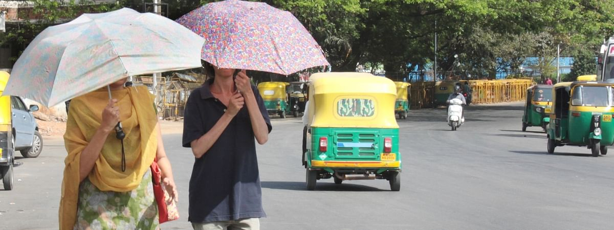 File photo of people using umbrellas to protect themselves from the scorching sun in Bengaluru, on March 7, 2019.