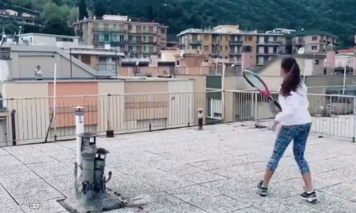 Two young girls play tennis across the rooftops of their buildings during the countrywide lockdown to curb the spread of COVID-19, in Liguria, Italy.