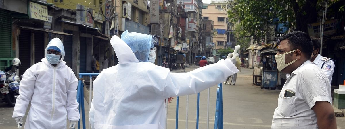 Health workers wearing Personal Protective Equipment (PPE) suits conducting thermal screening of people for COVID-19 during the extended nationwide lockdown imposed to contain the spread of coronavirus; at Howrah near Kolkata on April 18, 2020.
