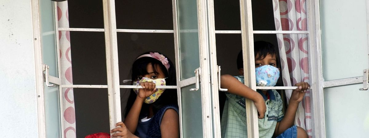 Children wearing masks looking out of the window of their house during  the nationwide lockdown to contain the spread of the coronavirus, in Patna, Bihar on April 1, 2020.