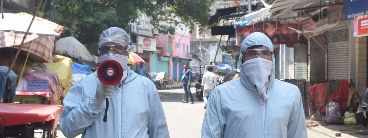 Police personnel wearing Personal Protective Equipment (PPE) suits makin announcements instructing people to stay indoors in Delhi's Sadar Bazaar during the extended nationwide lockdown imposed to mitigate the spread of coronavirus; on April 22, 2020.