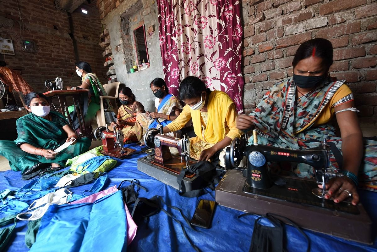 Women stitching cloth masks at their home amid the COVID-19 pandemic during the extended nationwide lockdown imposed to mitigate the spread of coronavirus, in Patna on April 29, 2020.
