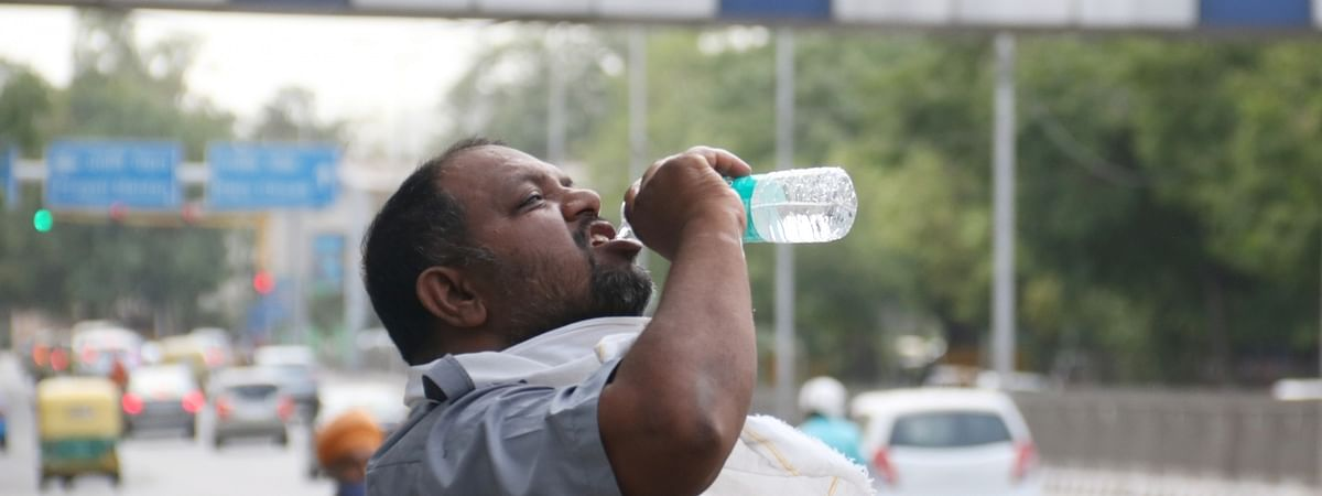 A man drinking some water to cool himself on a hot day in New Delhi on May 23, 2020.
