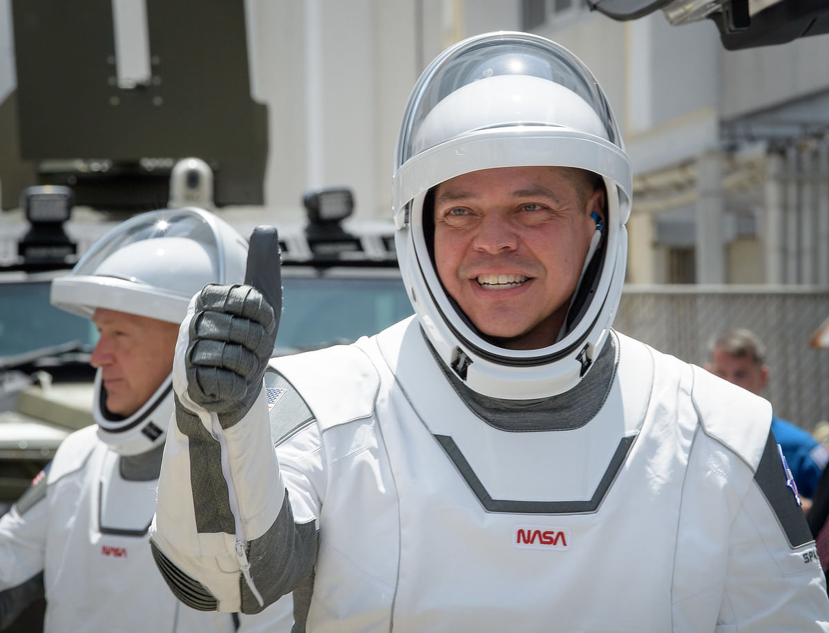 NASA astronauts Robert Behnken, foreground, and Douglas Hurley, wearing SpaceX spacesuits, are seen as they depart the Neil A. Armstrong Operations and Checkout Building for Launch Complex 39A to board the SpaceX Crew Dragon spacecraft for the Demo-2 mission launch, Saturday, May 30, 2020, at NASA's Kennedy Space Center in Florida.