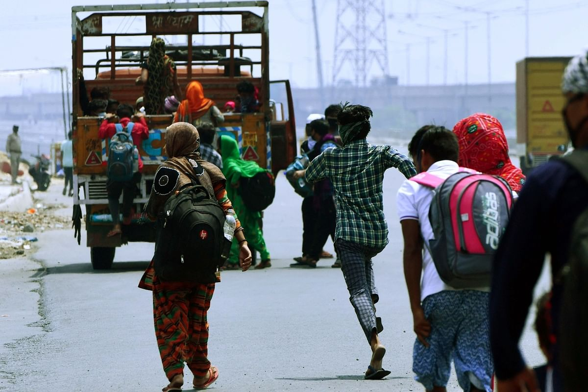 Migrant workers board a truck to reach their native places during the nationwide lockdown imposed to mitigate the spread of the coronavirus, on NH24 in Ghaziabad, Uttar Pradesh, on May 14, 2020.