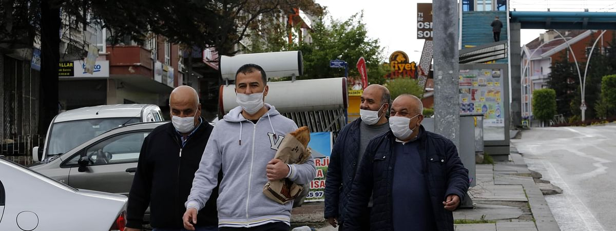 People wearing face masks walking on a street during a curfew in Ankara, Turkey, May 3, 2020.
