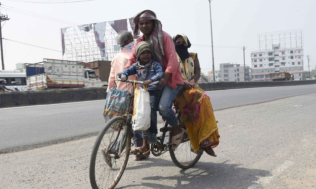 A migrant worker and his family on a bicycle on a deserted Patna street on the way to their native place during the nationwide lockdown imposed to contain the spread of the coronavirus pandemic, on May 16, 2020.