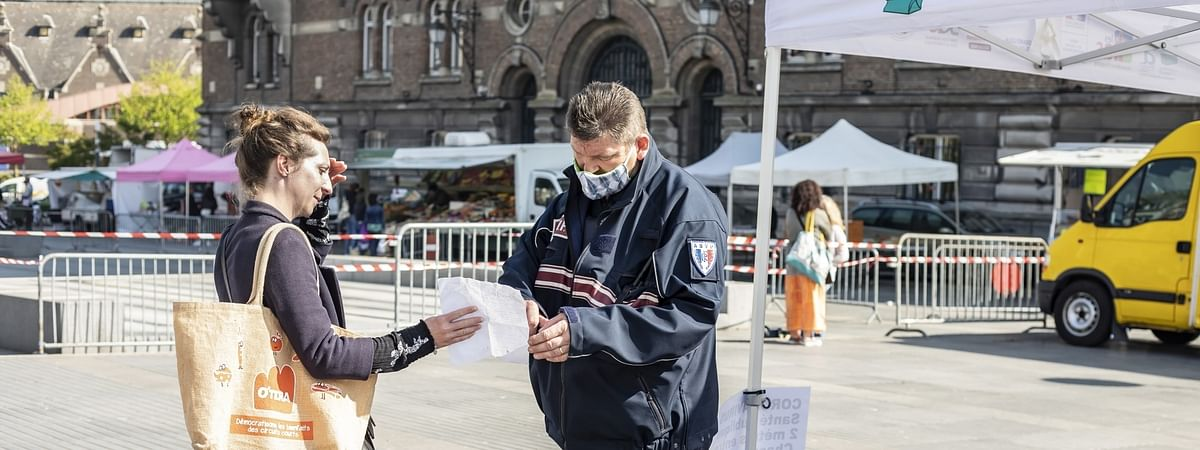 A policeman checks a resident at an open-air market in Armentieres, northern France, on April 17, 2020.