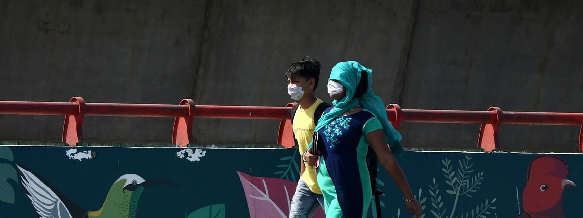 People, wearing protective masks, walking on a deserted road on a hot summer day during the nationwide lockdown, in New Delhi on May 25, 2020.
