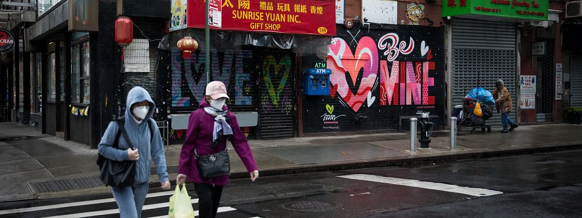 Pedestrians wearing face masks walkin across a street in New York, in the United States, on May 8, 2020.
