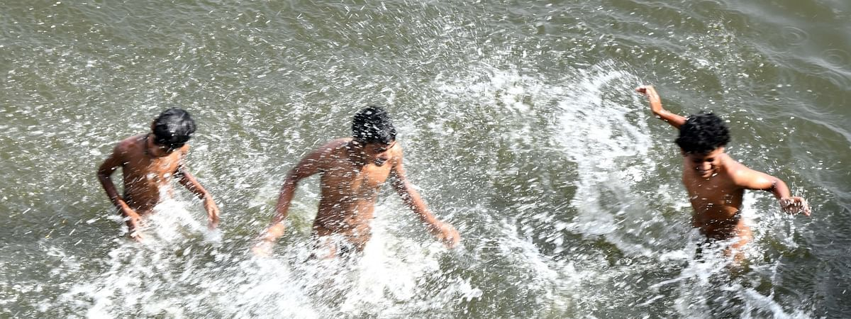 Children enjoying themselves in water on a hot day in New Delhi on May 23, 2020.