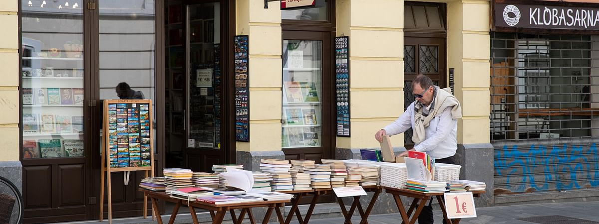 A man looking at a book in front of a bookstore in Ljubljana, Slovenia, on May 8, 2020.
