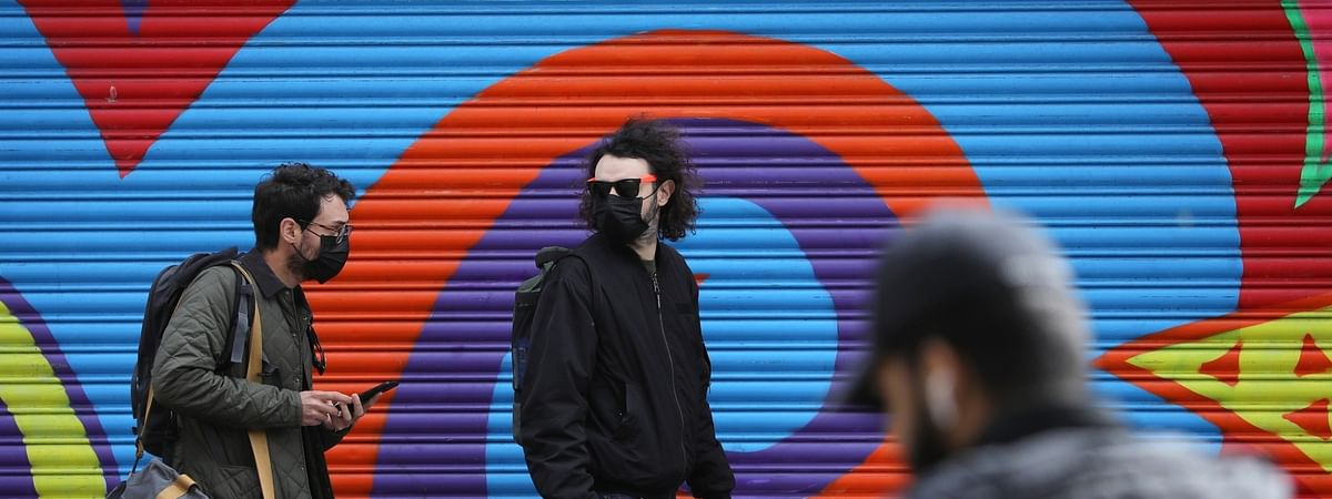 People walk past a closed shop in Hackney of London, Britain on April 17, 2020.