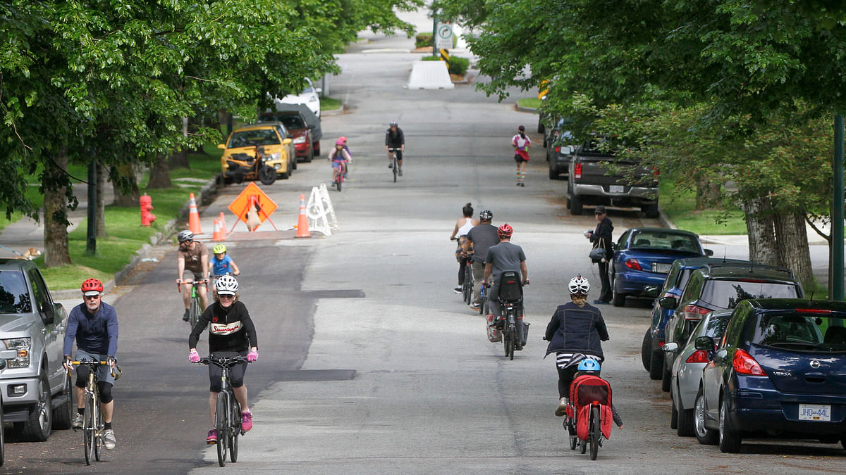 """People cycle and jog on the """"Slow Street"""" on a road in Vancouver, Canada, on May 24, 2020. The city of Vancouver unveiled the """"Slow Streets"""" program allowing people to walk and bike on the roads with limited local traffic in order to provide more space to the people to maintain physical distance."""