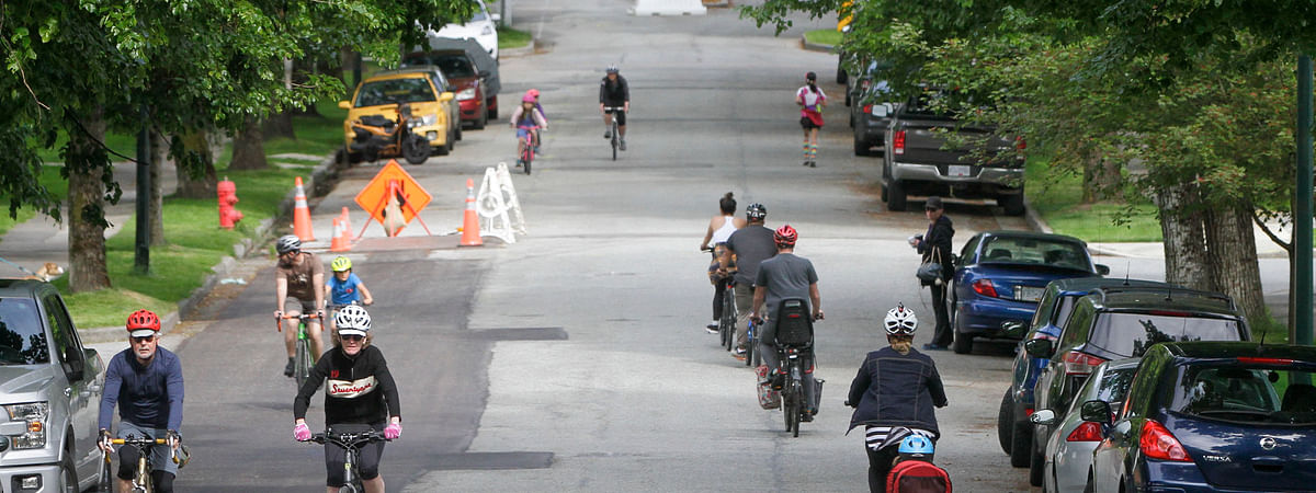"People cycle and jog on the ""Slow Street"" on a road in Vancouver, Canada, on May 24, 2020. The city of Vancouver unveiled the ""Slow Streets"" program allowing people to walk and bike on the roads with limited local traffic in order to provide more space to the people to maintain physical distance."