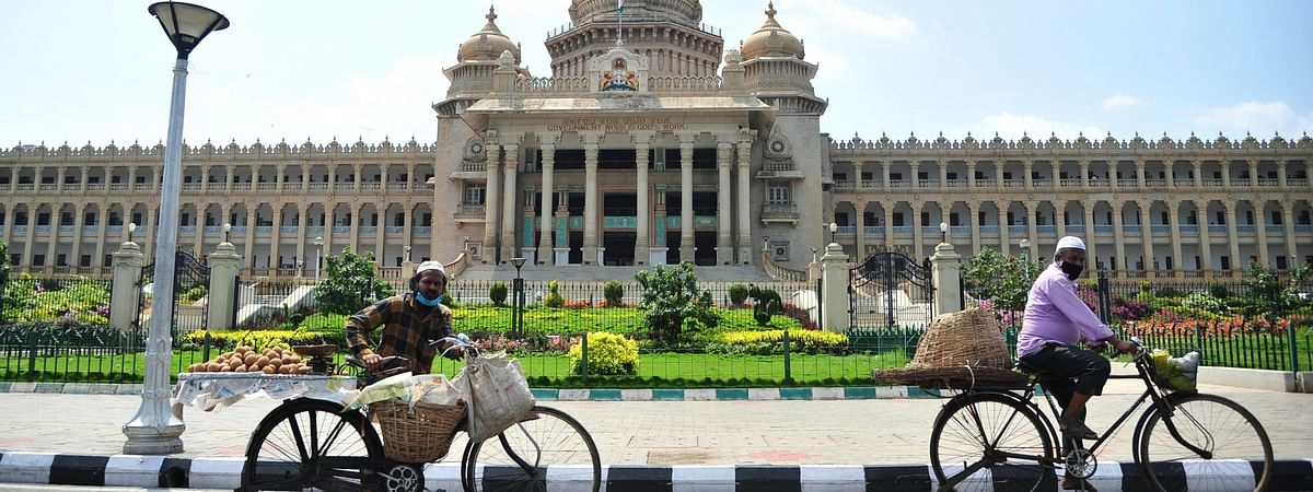 Fruit vendors pedal past Vidhana Soudha during the extended nationwide lockdown imposed to contain the spread of coronavirus, in Bengaluru on May 1, 2020.