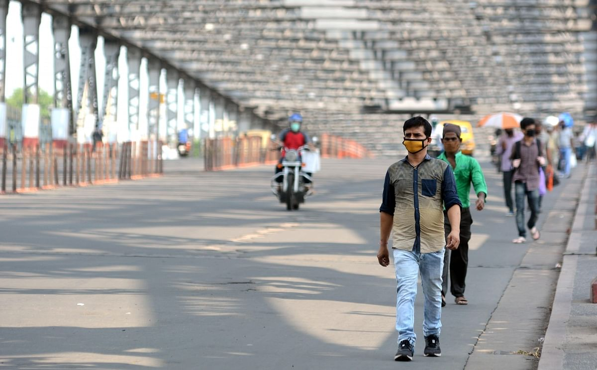 People crossing the usually busy Howrah Bridge that now wears a deserted look during the nationwide lockdown imposed to contain the spread of coronavirus, in Kolkata on May 15, 2020.