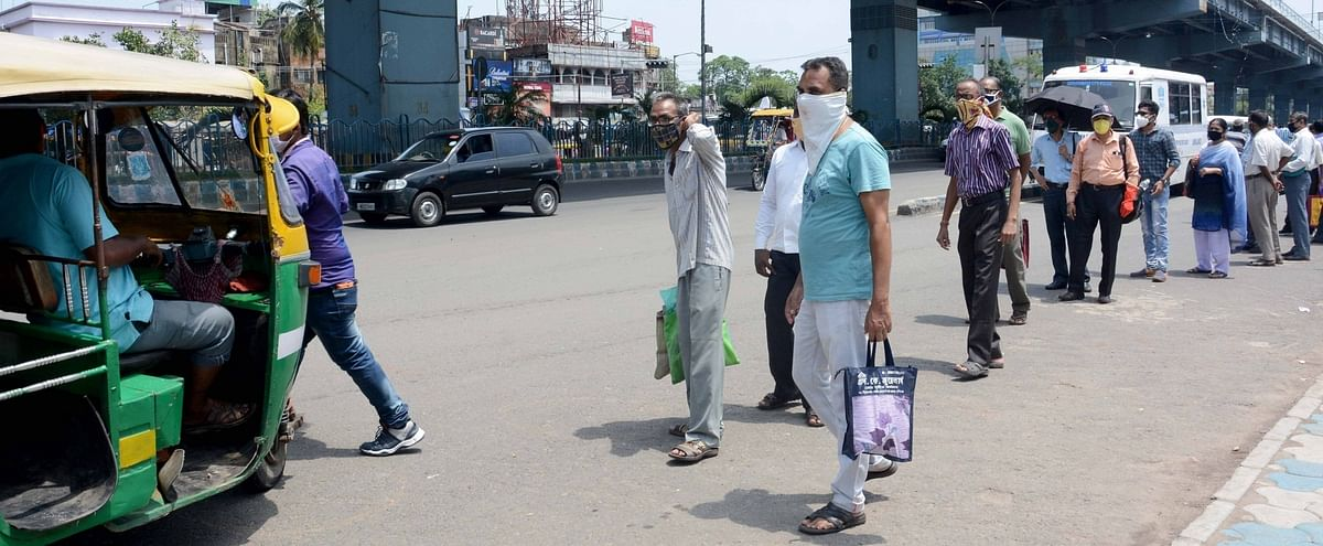 People wearing masks and maintaining social distancing while waiting in queues for autorickshaws during the nationwide lockdown imposed to contain the spread of coronavirus, in Kolkata on May 29, 2020.