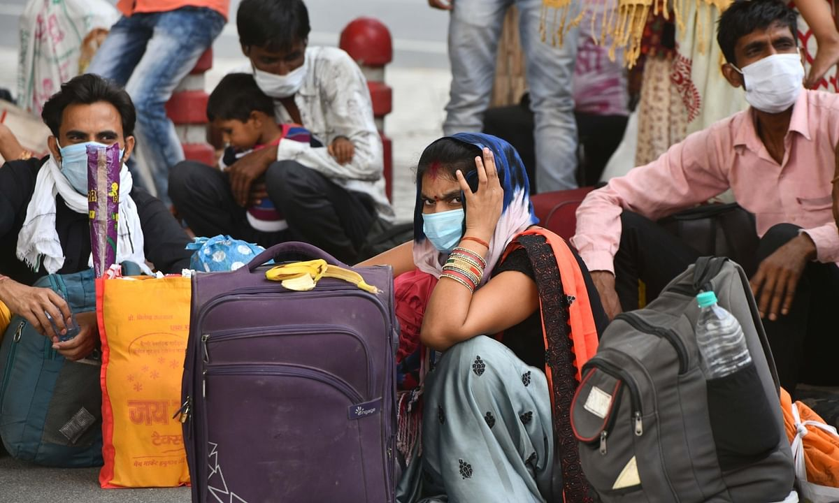Migrant workers and their families sit along with their belongings as they wait to board buses to their respective native places, in Noida near Delhi during the nationwide lockdown imposed to mitigate the spread of coronavirus, on May 17, 2020.