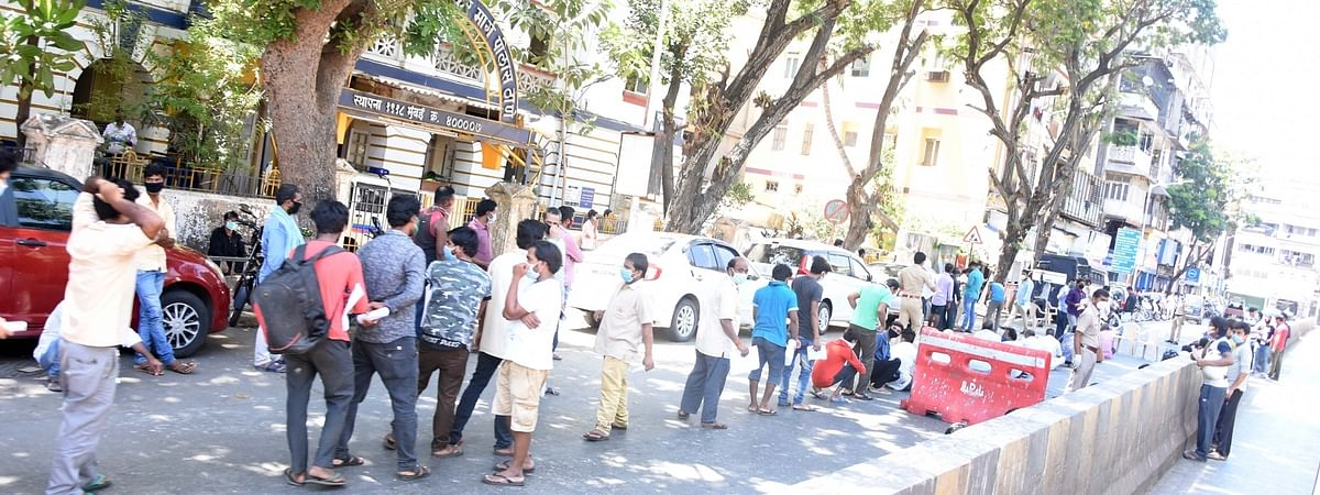 Migrant labourers stuck in Mumbai due to the ongoing nationwide lockdown imposed to mitigate the spread of COVID-19 queue up outside the Dadasaheb Bhadkamkar Marg Police Station to collect certificates from the police before leaving for their hometowns, on May 7, 2020.