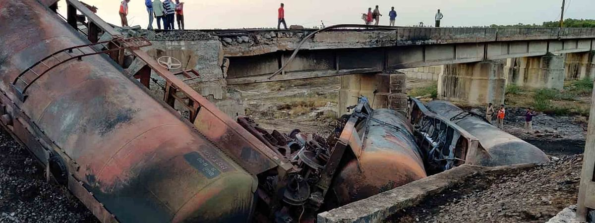 View of a goods train, with diesel tankers, which derailed at Turpu Naidu Palem between Surareddy Palem and Tangutur railway stations in Prakasam district of Andhra Pradesh, on June 25, 2020. As a result of the accident, five tankers fell into the Musi river from a rail overbridge, just beside the habitation, Bapuji Colony, and four of them caught fire.
