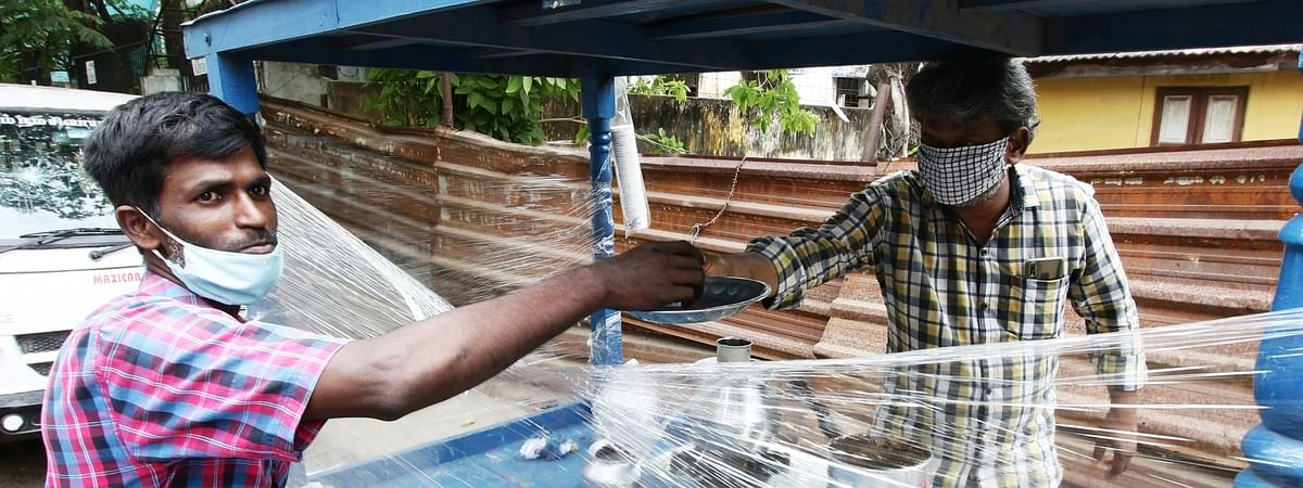 A tea vendor puts up a plastic sheet on his cart as a precautionary measure against COVID-19 as he sells tea on a hot day in Chennai on June 10, 2020.