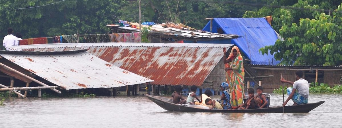 Villagers row their boat through floodwaters in Sildubi village following heavy rainfall that left Assam's Morigaon district inundated, on June 28, 2020.