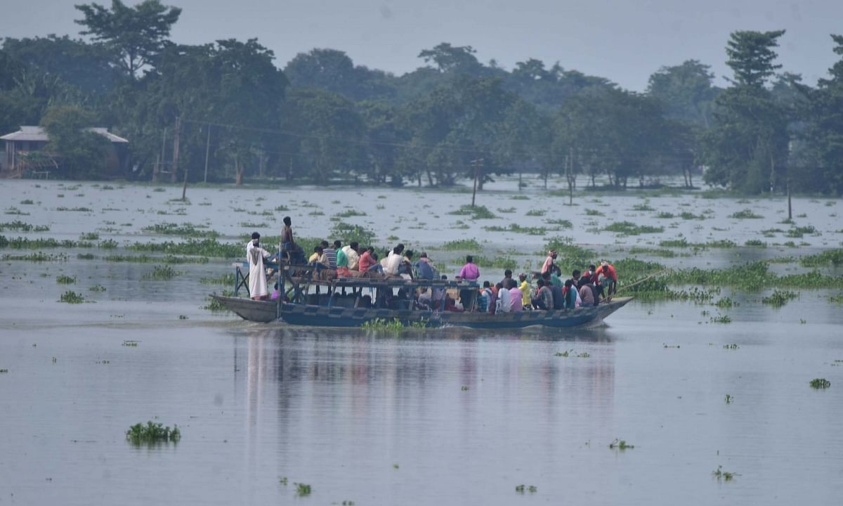 Villagers rowing their boat through the floodwaters as they move to take shelter at a highland after heavy rains left the Sildubi village submerged under water in the flood-hit Morigaon district of Assam on June 29, 2020