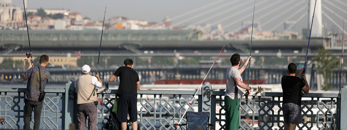 People fishing on the Galata Bridge in Istanbul, Turkey, on June 9, 2020. After the government eased the COVID-19 restrictions last week, more than 500 fishermen each day flock to the bridge, a hot spot fishing location in the European part of the city, spanning the Golden Horn.