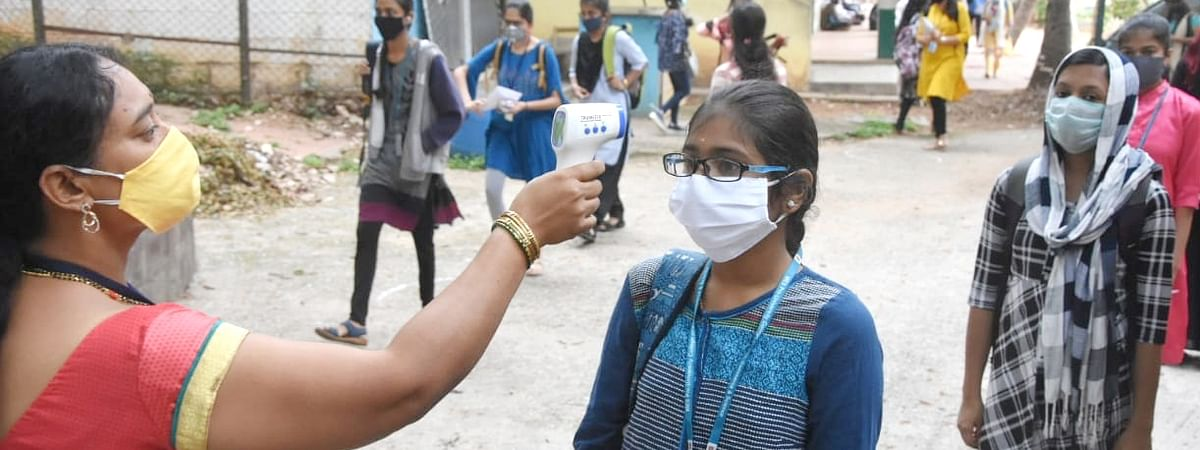 A student being screened for COVID-19 as she arrives to appear for Karnataka Board Class 12 Examinations postponed due to the ongoing nationwide lockdown imposed to contain the spread of the coronavirus, in Bengaluru on June 18, 2020.