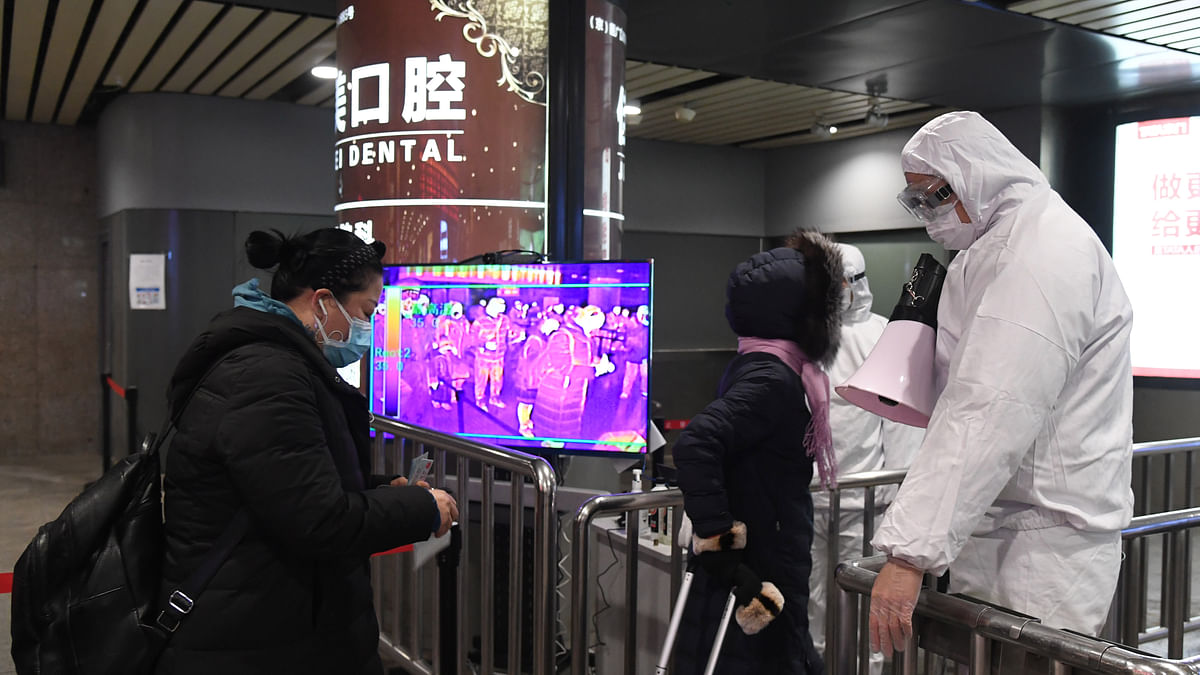 File photo of health workers checking passengers' temperature at the exit of Beijing West Railway Station in Beijing, capital of China.