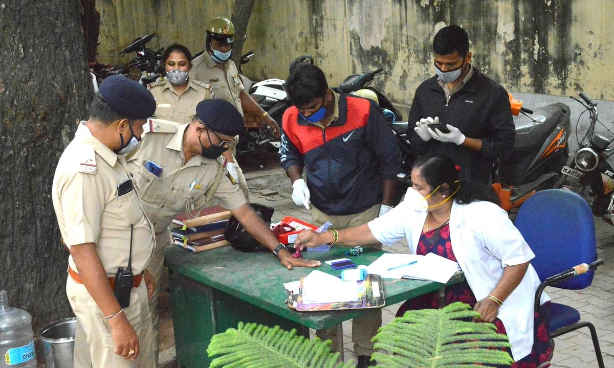 Police personnel get ther hands stamped after undergoing COVID-19 screening at the Cubbon Park police station that has been sealed off after a constable tested positive for the coronavirus, in Bengaluru on June 20, 2020.