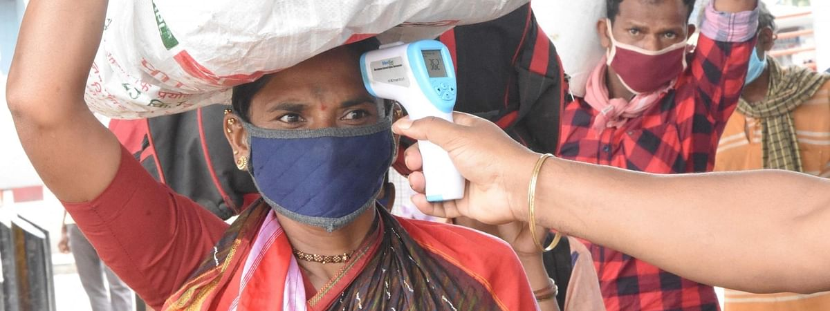 Migrants being screened for symptoms of COVID-19 as they arrive at a bus depot to head back to their native villages after the Bengaluru district authorities re-imposed a lockdown across the city from Tuesday to July 22 for containing the corona virus spread, on July 13, 2020.