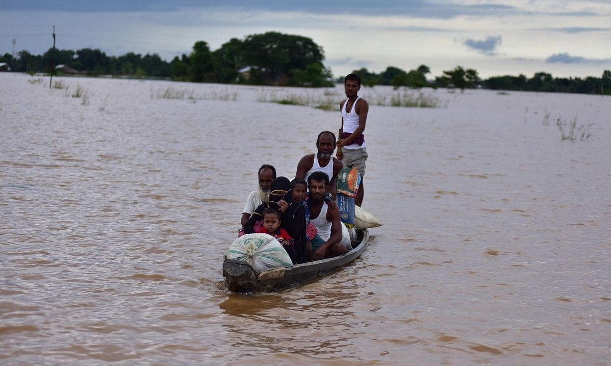 Members of a family sail through the flood waters on a boat in search of a safer place in Assam's flood affected Nagaon district on July 22, 2020.