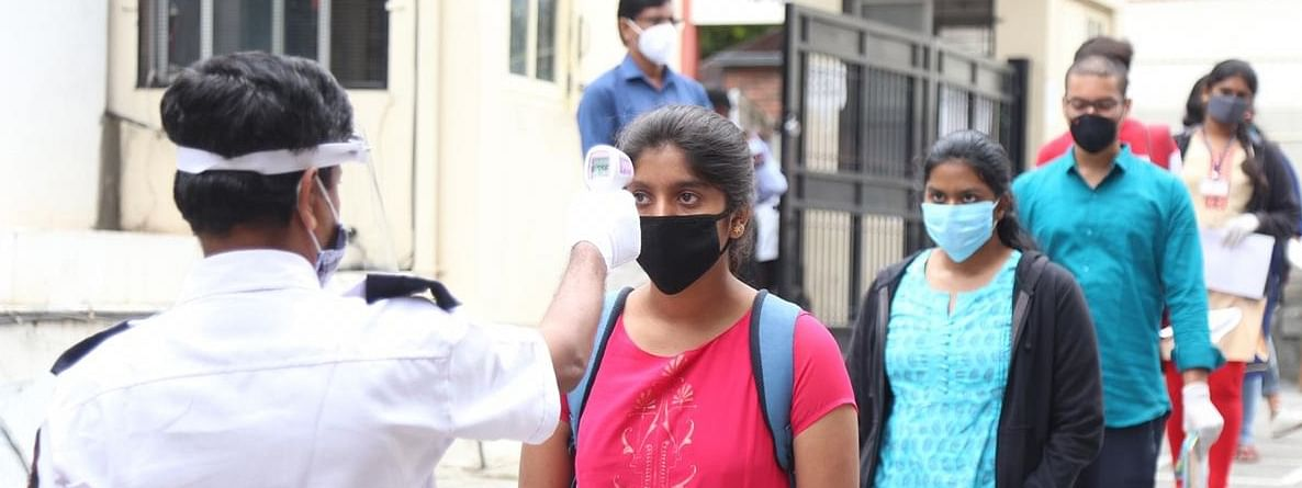 Candidates undergoing temperature check to detect fever as an indicator of possible COVID-19 infection as they arrive to appear for the Common Entrance Test (CET) examinations at SSMRV college in Bengaluru on July 30, 2020.
