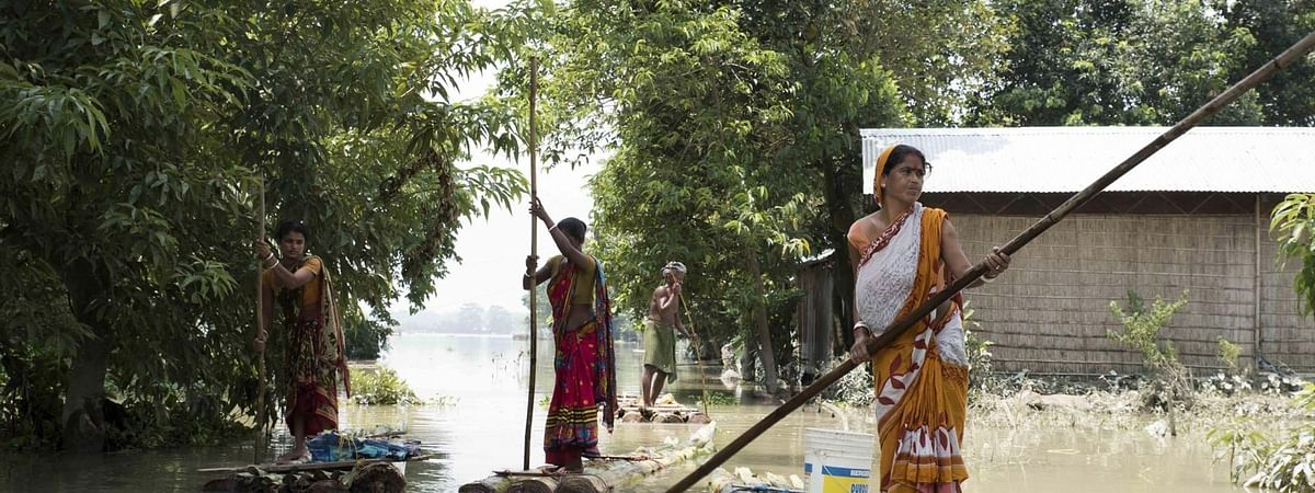 Women using banana rafts to move across in the flood-affected Morigaon district of Assam.