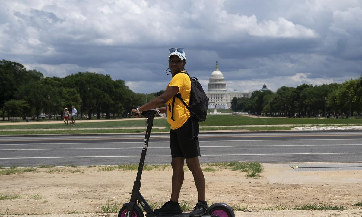 A woman rides a scooter on the National Mall in Washington, D.C., the United States, July 11, 2020.