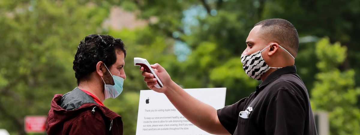 A staff worker checks the body temperature of a customer outside an Apple store on Fifth Avenue of New York City, the United States, on June 17, 2020