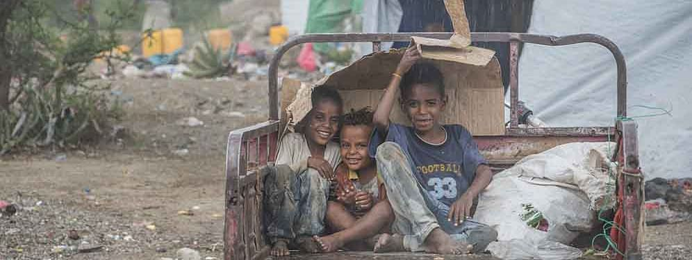 Children taking shelter from the rain at a camp for newly displaced Yemenis near the town of Al-Dhale. Yemen is experiencing a protracted humanitarian crisis.