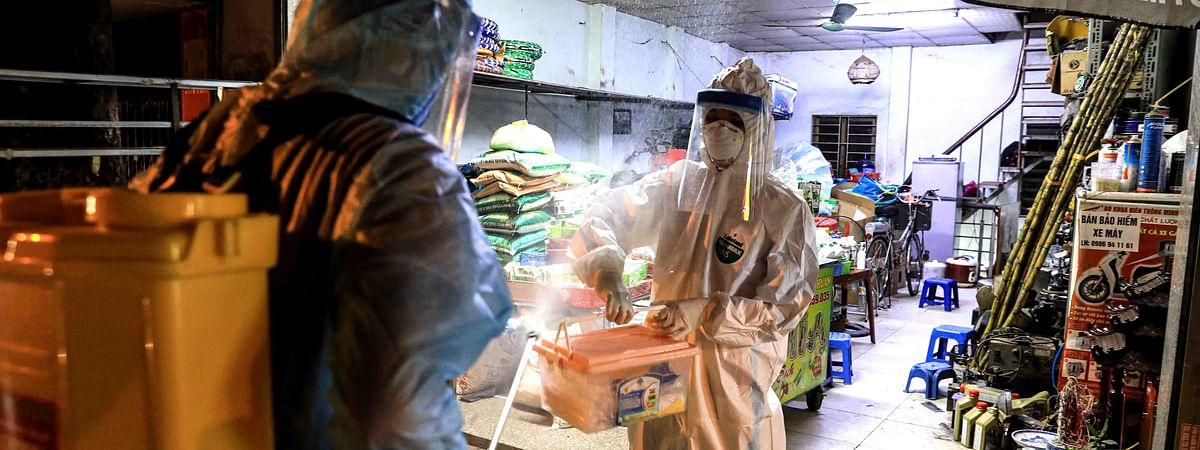 Medical workers disinfecting an alley where a suspected COVID-19 patient lives, in Hanoi, Vietnam, on July 29, 2020.