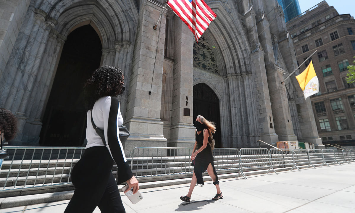 Pedestrians walking past St. Patrick's Cathedral on Fifth Avenue in New York, the United States, July 4, 2020.
