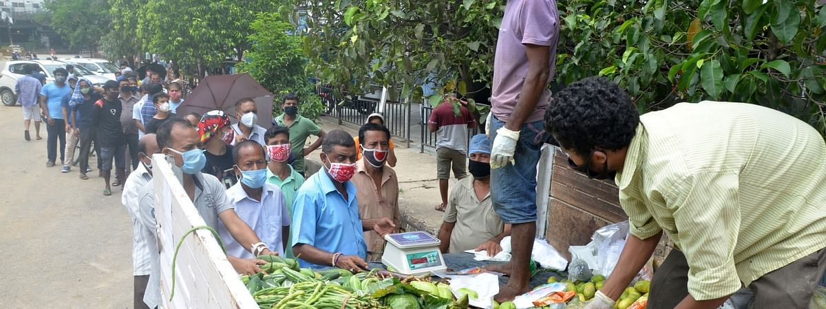 People buying vegetables from government vendors after the authorities re-imposed a total lockdown to curb the spread of the novel coronavirus, at Ganeshguri in Guwahati on July 8 , 2020.
