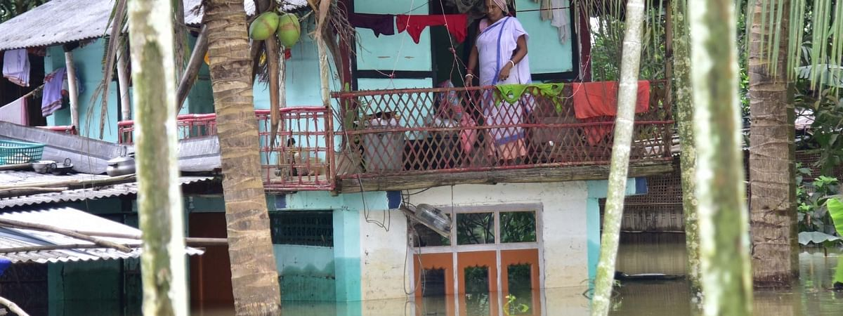 A woman stands on the upper floor of her house partially submerged under water at Baghmari village in Assam's flood hit Nagaon district on July 14, 2020.