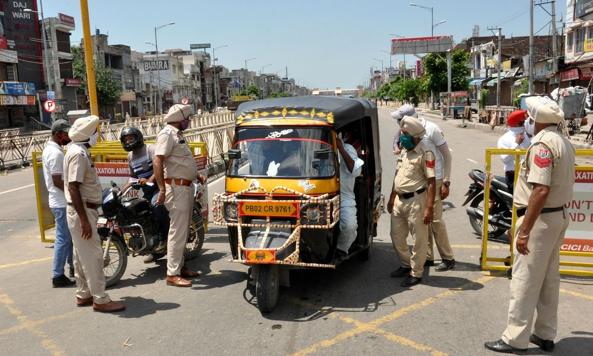 Police personnel inspecting a vehicle at a police check-post during the weekend lockdown imposed by the Punjab Government across the state in the wake of COVID-19 pandemic, in Amritsar on August 22, 2020.