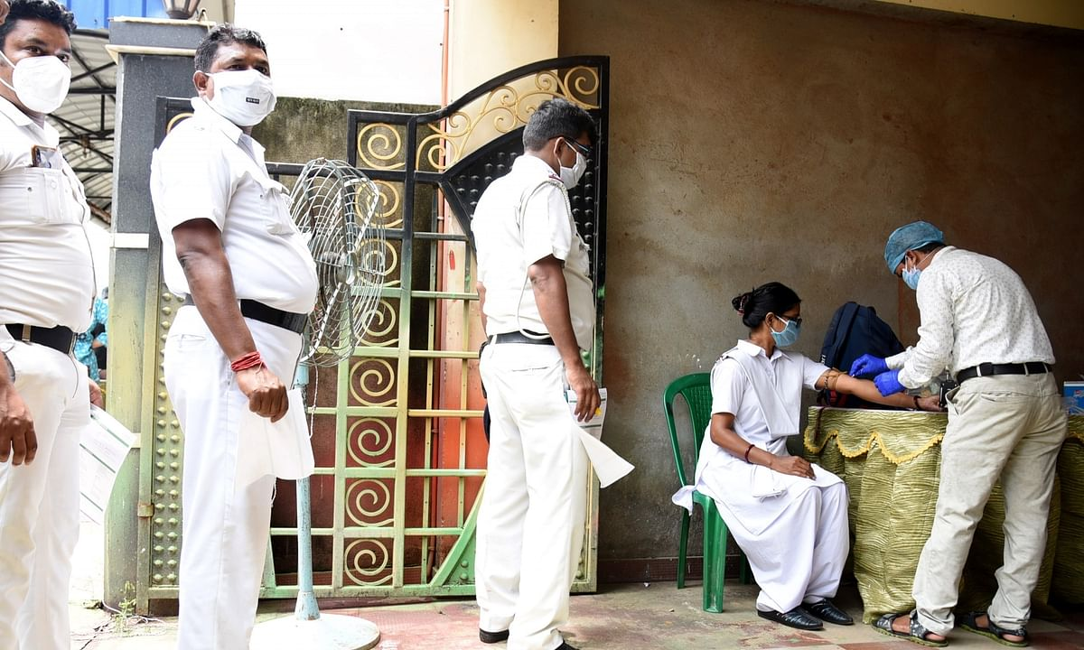 A health worker collecting a swab sample from police personnel and residents  for antibodies test of COVID-19, in Kolkata on August 23, 2020.