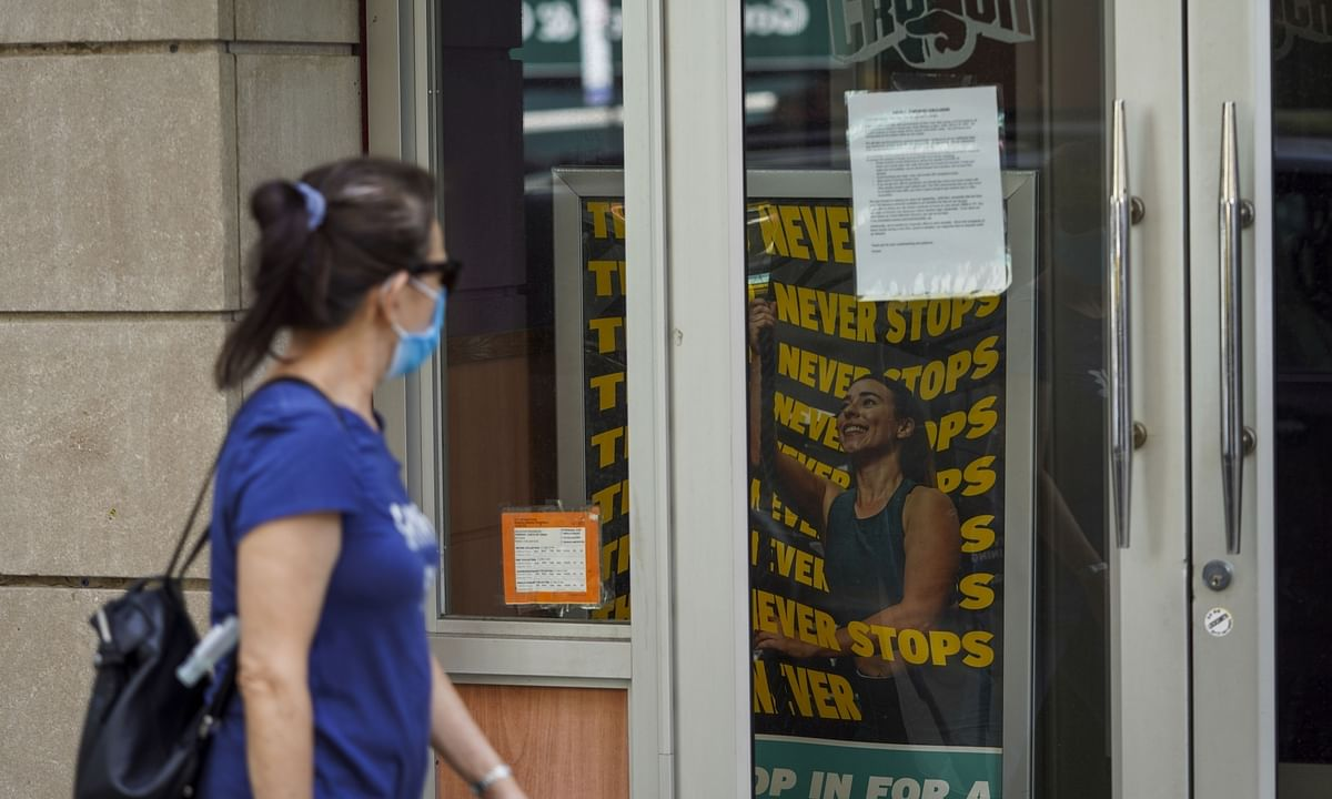 A pedestrian walks past a temporarily closed fitness center in New York, the United States, on August 18, 2020.