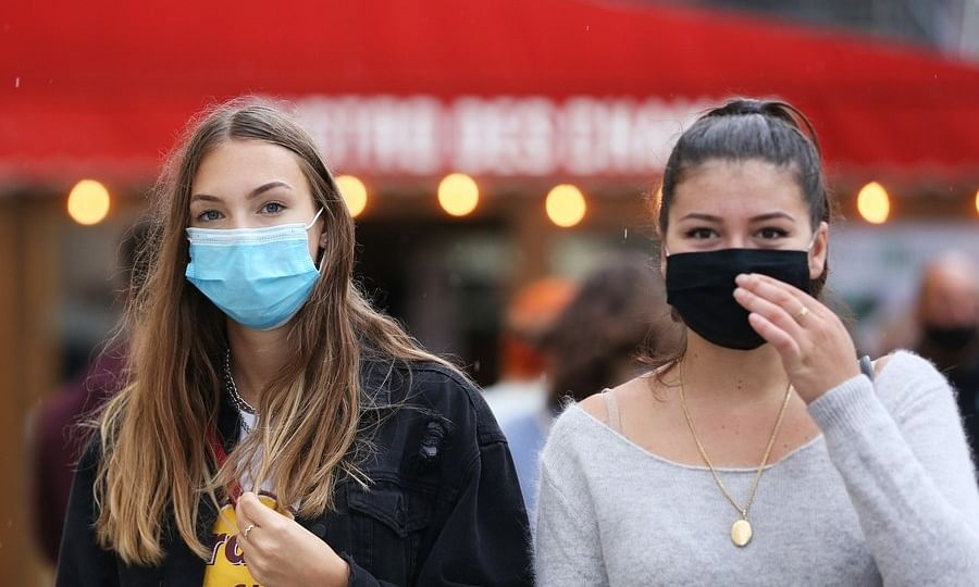 People wearing face masks walking on the Champs Elysees Avenue in Paris, France, on August 28, 2020