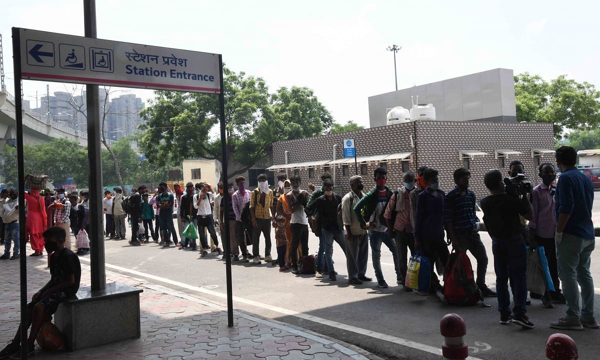 Migrant workers queuing up to give swab samples for COVID-19 testing as they arrive at the Anand Vihar Bus Terminal in New Delhi on August 18, 2020.