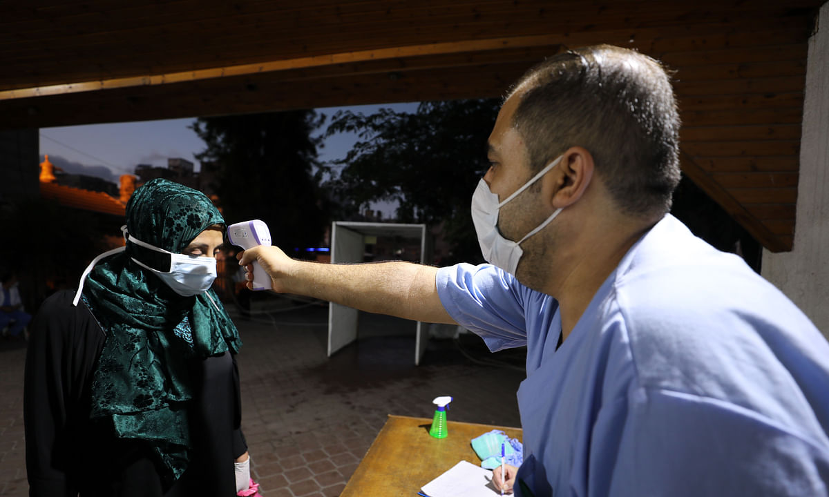 A Palestinian health worker measuring the body temperature of a woman at Al Amal hospital, in the southern Gaza Strip city of Khan Younis, on August 28, 2020.